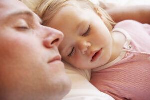 photo of father and baby daughter sleeping in bed